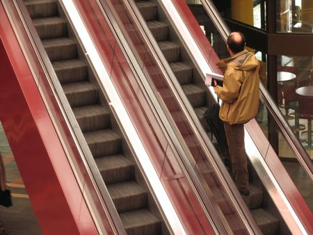 Man going up with the escalator in a cultural center. photo