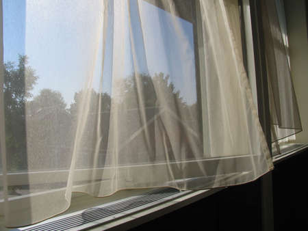 curtain window: Curtains blowing in the wind a hot summer day. Stock Photo