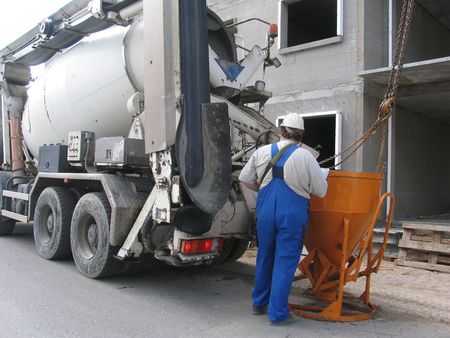 Man and concrete truck at building site.