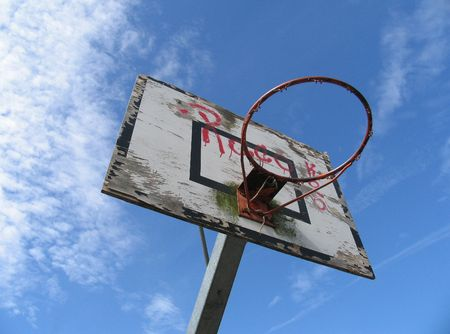 Old outdoor basket hoop against the blue sky. photo