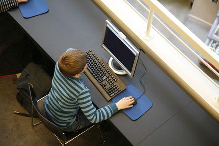 Boy using a PC in a public library Denmark. - Focus on keyboard... natural lighetening. Stock Photo