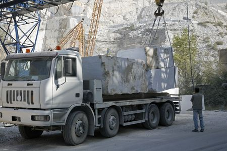 carrara: Marble quarry in the mountains near Carrara - Tuscany - Italy. A lorry is being loaded with big blocks of marble.