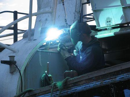 Welder repairing a fishing wessel. photo