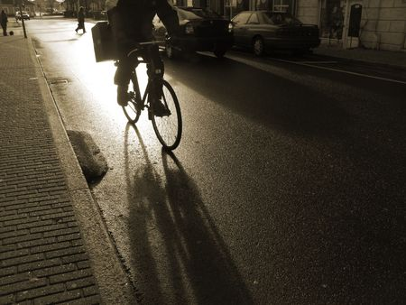 Cyclist on his way to work early in the morning after rain. Duotone. Stock Photo
