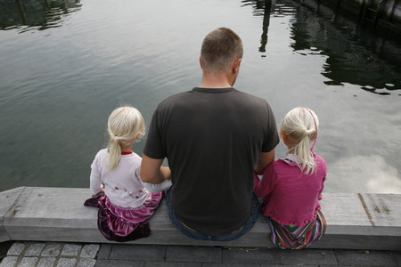Father with his two small girls sitting looking for fish in the water.