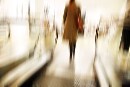 Female going up with the escalator in a department store - motion blur.