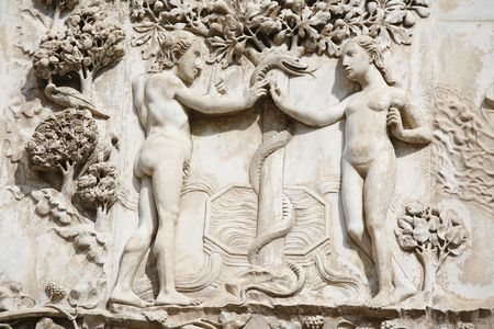 Adam and Eve in the Garden of Eden in front of the tree of knowledge. Detail from the ornate of the facade - Orvieto Cathedral, Umbria, Italy Stock Photo