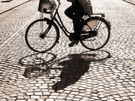 cobblestone street:  A warm spring afternoon a young girl is biking through the old streets of Copenhagen, Denmark.                       Stock Photo