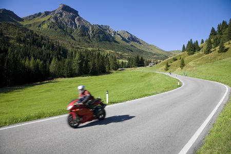 Speedy motorbike on mountain road - Dolomites, Italy. photo