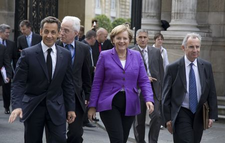 PARIS, FRANCE - JUNE 11 - 2009: French president Nicolas Sarkozy ( left) and German chancellor Angela Merkel ( middle) outside the Elysee Palace on their way to lunch.