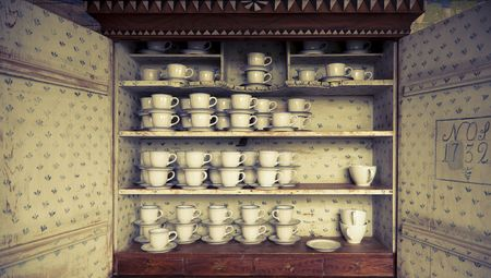 cross processed: Beautiful antique Swedish cupboard from 1732 filled with cups. Cross processed to underline the mood. Stock Photo