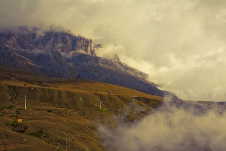 Early September morning with low hanging clouds in the Dolomites. Image is cross processed and a little film grain added to reflect age. Stock Photo - 8196365
