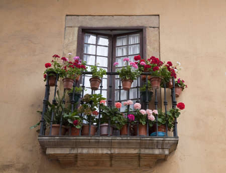 Beautiful tiny balcony with Geranium in many red colors - urban Oviedo, Spain  photo