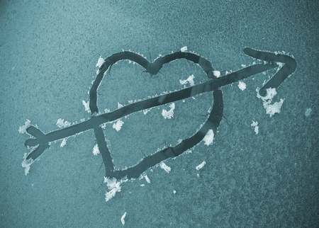 Heart with arrow scraped on a frozen automobile windscreen in the morning. photo