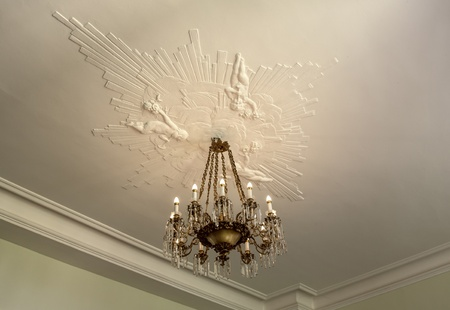 Nice vintage ceiling with old chandelier and beautiful artistic stucco. photo