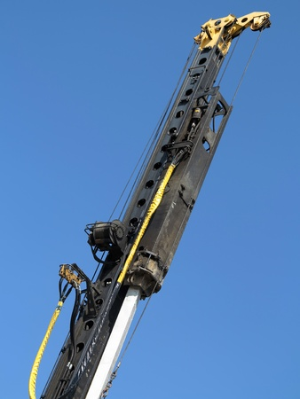 piling: Pile-driver in action against the blue sky.