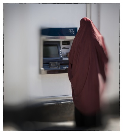 cashpoint: Unidentified muslim woman seen from behind by cashpoint drawing cash.