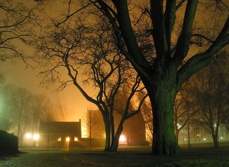 Foggy night in the park. Light streaming out of the church windows. Stock Photo