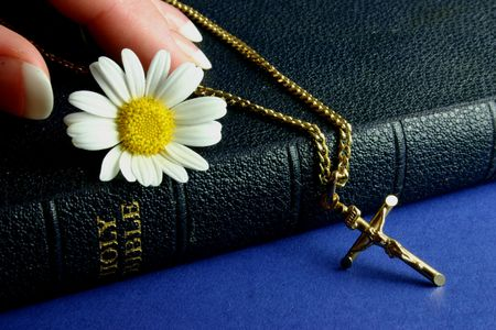 Hand touching bible with gold crucifix and flower photo