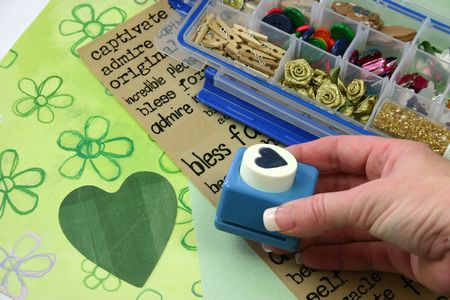 brads: A selection of scrapbooking  craft materials with hand holding cutter Stock Photo