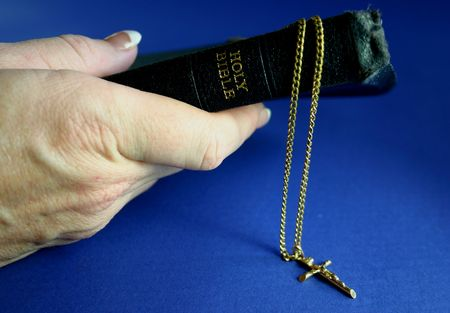 Hand holding bible with gold crucifix on chain photo