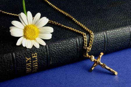 Old bible, with gold crucifix and daisy photo