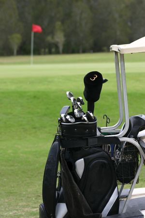 caddie: Close up of golf clubs on cart with green hole flag in background