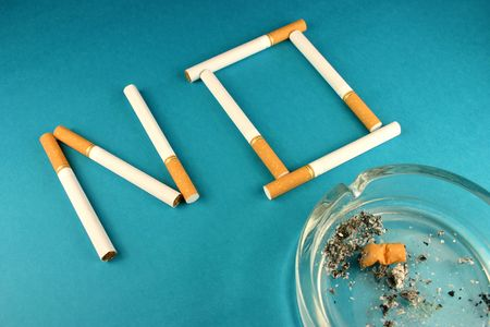 Cigarettes forming word NO on blue background with butt in ashtray photo