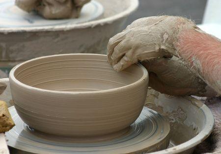 alfarero: Potter que forma el taz�n de fuente de la arcilla en la rueda Foto de archivo