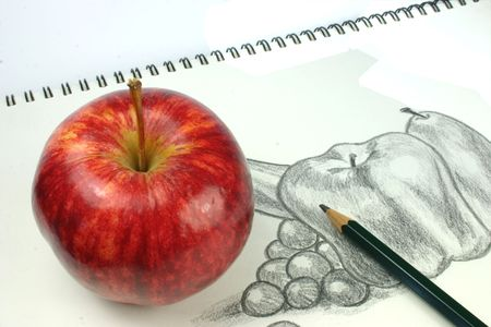 Red apple with still life fruit sketch in background with pencil photo