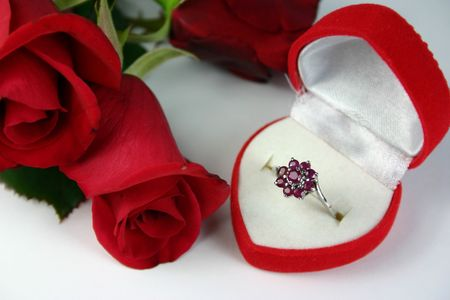 Ruby ring in heart shaped box with red rose buds photo