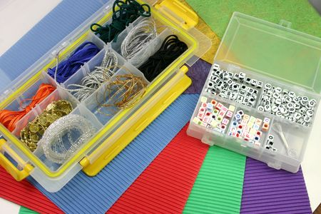 brads: a selection of craft materials in containers and coloured cardboard Stock Photo