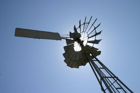 Windmill with sun behind it photo