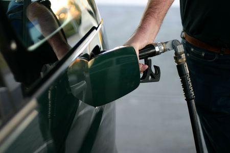 unleaded: Man refueling car at petrol station