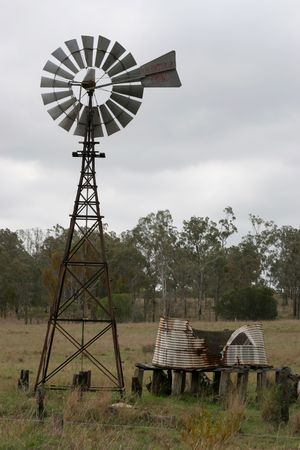 old water windmill and tank in rural area photo