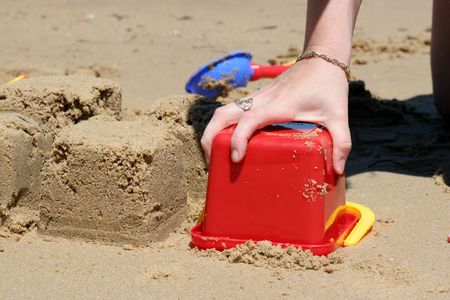 sandcastles: Close up of person building sandcastles on beach with red plastic bucket Stock Photo