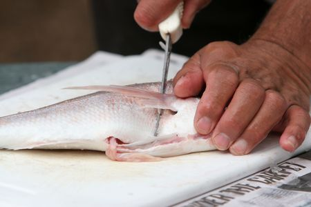 Close up of man filleting fresh fish with knife Stock Photo - 1193483