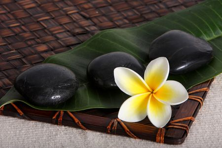 close up of hot  river stones with yellow and white frangiapani flower and leaf on bamboo matt - tropical day spa photo