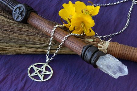 close up of wiccan objects - pentacle pendant wood  crystal wand and straw besom Stock Photo