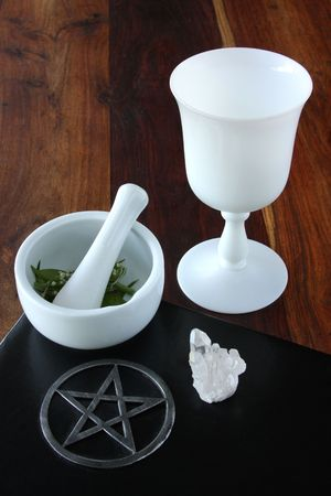 herbology: closeup of wicca spell tools and book of shadows with crystal cup mortar and pestle