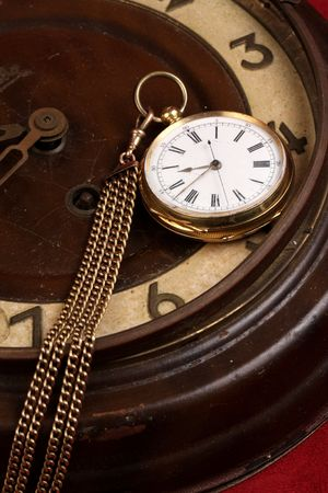 old gold fob pocket watch laying on antique clock Stock Photo