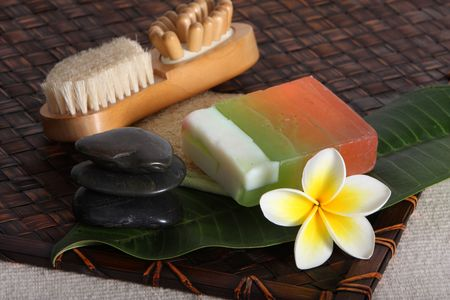 close up of hot massage river stones with yellow and white frangiapani flower and leaf with beauty day spa products - soap lotions and loofah photo