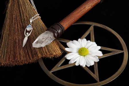 wicca: close up of wiccan objects - brass pentacle wand crystal and flower