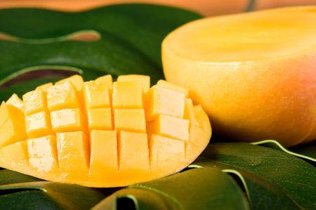 mango: ścieśniać świeżego tropikalne mango - cięcie na zielonych liści