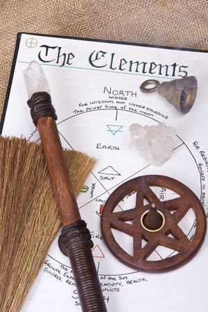 pentagram: wiccan tools on top of book of shadows with wand bell and pentacle incense burner