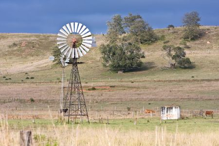 rural scene with windmill in country field photo