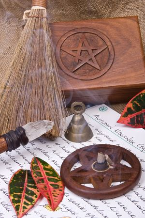wicca: wooden pentacle with incense burning with hand written book of shadows and fall leaves - autumn equinox mabon ritual Stock Photo