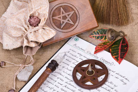 ладан: wooden pentacle with incense burning with hand written book of shadows and fall leaves - autumn equinox mabon ritual Фото со стока