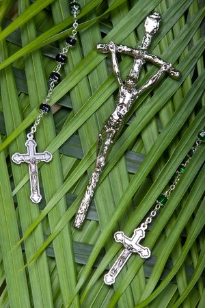 palm sunday: close up of rosaries and crucifx on palm leaves