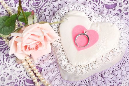 Close up of engagement ring on pink felt heart with rose and pearls in background photo